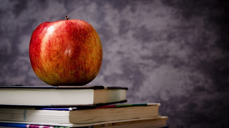 apple sitting on pile of books