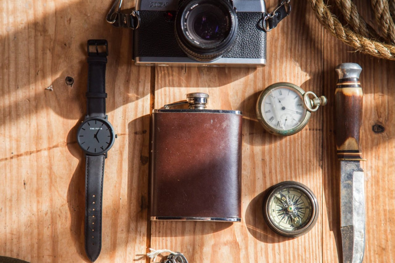 wooden table with flask, watch, camera, knife