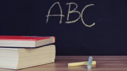 abc on blackboard next to books and chalk