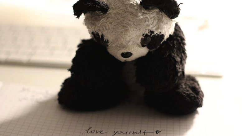 Pandabear sitting on paper that says i love you