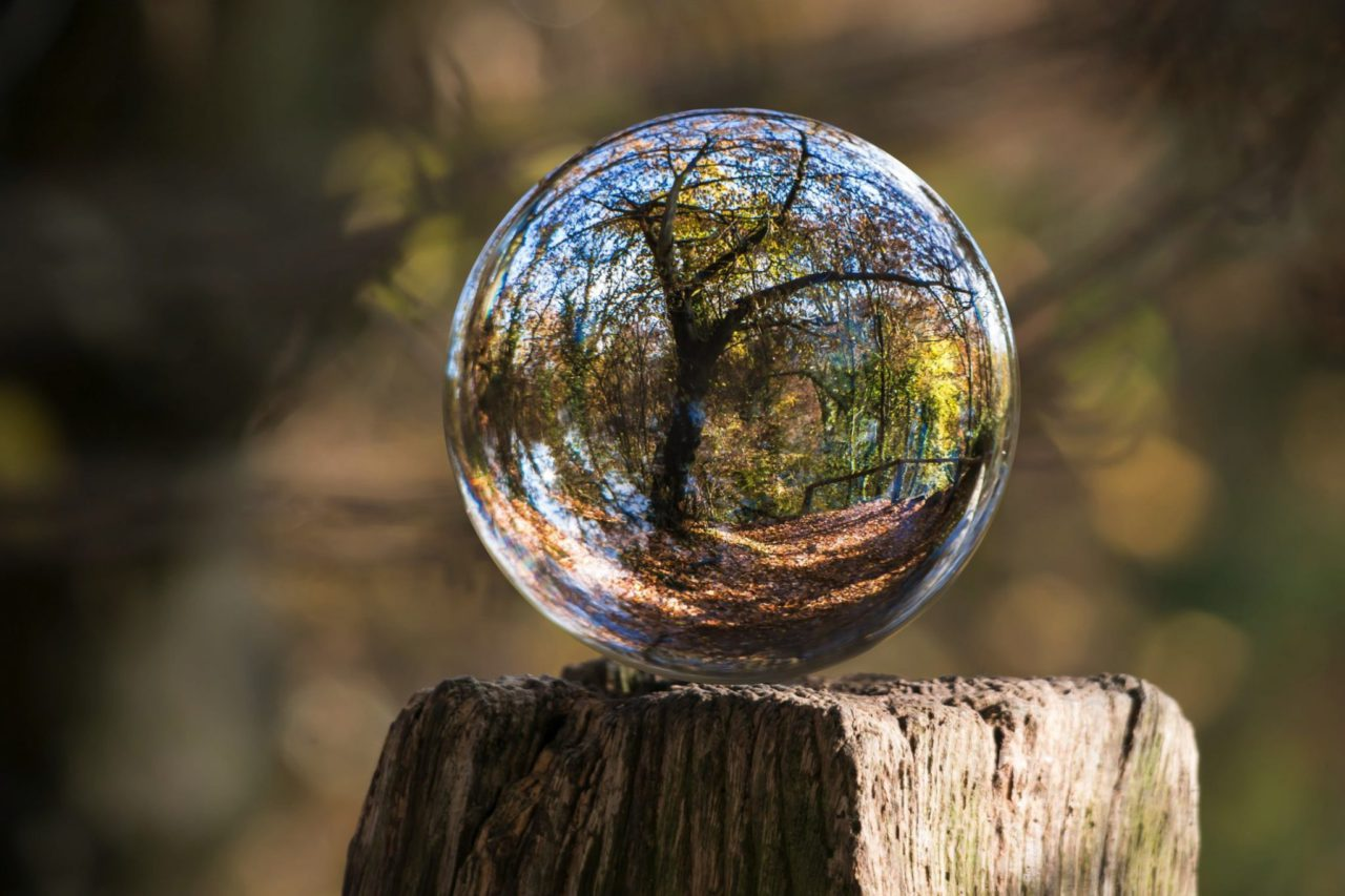 glass ball sitting on top of fence post