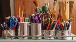 cups full of pens, pencils, paint brushes, and rulers