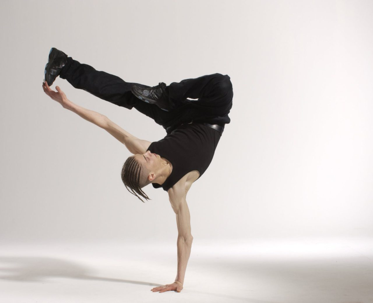 man wearing all black break dancing with a white background