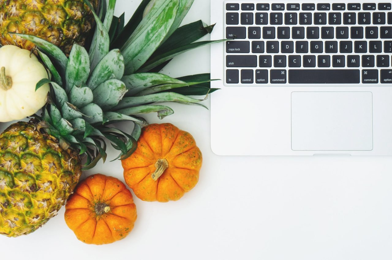 laptop next to a pineapple and some small pumpkins